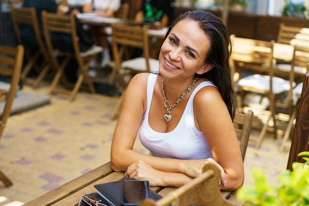 Tevreden jonge vrouw in wit t-shirt zit aan tafel van een straatcafé in de buitenlucht, aantrekkelijk werk op afstand...