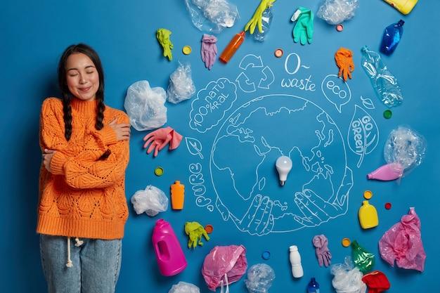 Tevreden jonge vrouwelijke activiste omhelst zichzelf, voelt troost, poseert tegen blauwe muur met plastic afval over de hele wereld, vecht tegen milieuvervuiling