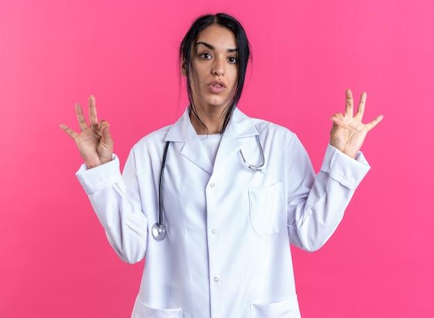 Tevreden jonge vrouwelijke arts die een medisch gewaad draagt met een stethoscoop die een goed gebaar toont dat op een roze muur wordt geïsoleerd