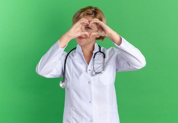 Tevreden jonge vrouwelijke arts die een medisch gewaad draagt met een stethoscoop die een hartgebaar toont dat op een groene muur wordt geïsoleerd