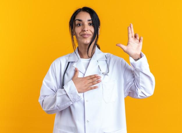 Tevreden jonge vrouwelijke arts die een medisch gewaad draagt met een stethoscoop die een pistoolgebaar toont dat op een gele muur wordt geïsoleerd