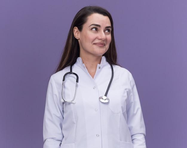 Tevreden jonge vrouwelijke arts die een medisch gewaad met een stethoscoop draagt, kijkt naar de zijkant