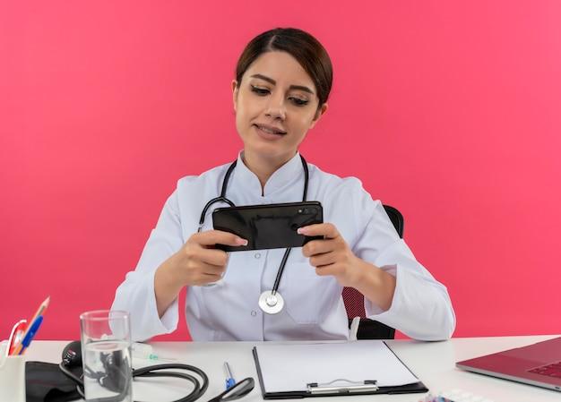 Tevreden jonge vrouwelijke arts die medische mantel en stethoscoopzitting aan bureau met medische hulpmiddelen en laptop draagt die mobiele telefoon met behulp van die op roze muur wordt geïsoleerd