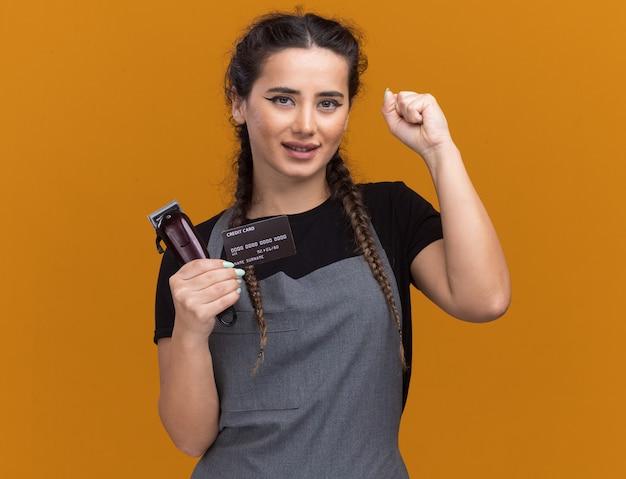 Tevreden jonge vrouwelijke kapper in uniform met creditcard en tondeuse met ja gebaar geïsoleerd op oranje muur