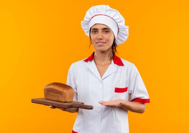 Tevreden jonge vrouwelijke kok die chef-kok eenvormige holding en punten met hand aan brood op scherpe raad op geïsoleerde gele muur met exemplaarruimte draagt