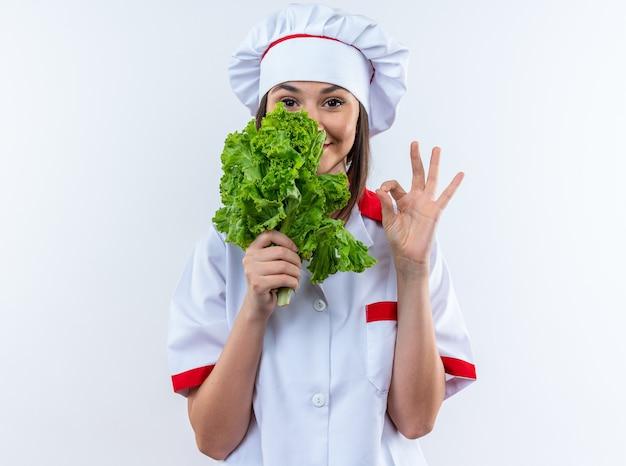 Tevreden jonge vrouwelijke kok die chef-kok uniform draagt die salade houdt die oke gebaar toont dat op witte muur wordt geïsoleerd