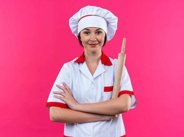 Tevreden jonge vrouwelijke kok die chef-kokuniform draagt die deegroller houdt die handen kruist die op roze muur worden geïsoleerd