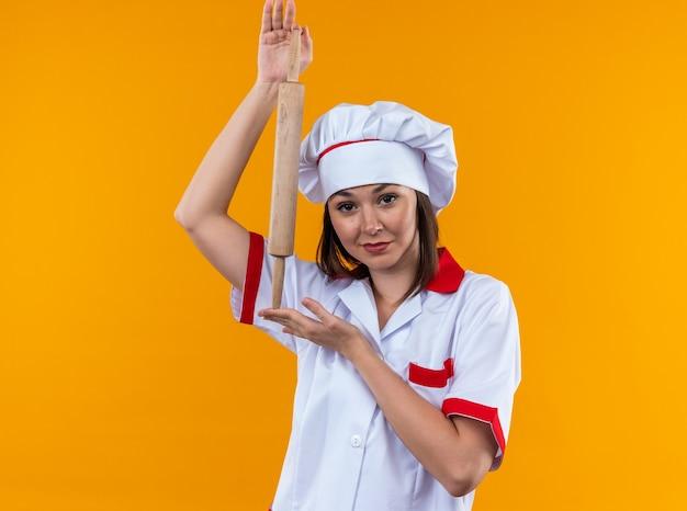 Tevreden jonge vrouwelijke kok die chef-kokuniform draagt die deegroller houdt die op oranje muur wordt geïsoleerd
