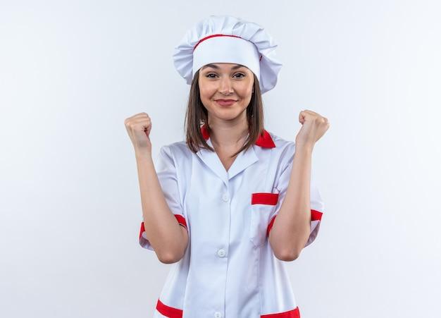 Tevreden jonge vrouwelijke kok die chef-kokuniform draagt die ja gebaar toont dat op witte muur wordt geïsoleerd