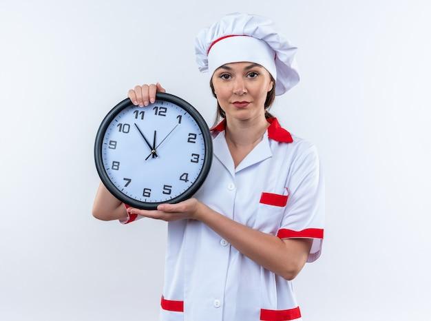 Tevreden jonge vrouwelijke kok die chef-kokuniform draagt die muurklok houdt die op witte muur wordt geïsoleerd