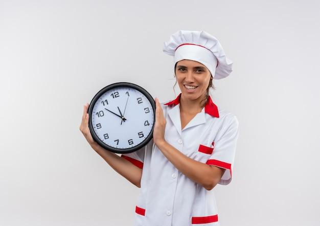 Tevreden jonge vrouwelijke kok die de muurklok van de chef-kok eenvormige holding met exemplaarruimte draagt