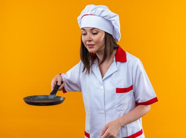 Tevreden jonge vrouwelijke kok die een chef-kok uniform draagt en naar een koekenpan kijkt die op een oranje achtergrond wordt geïsoleerd