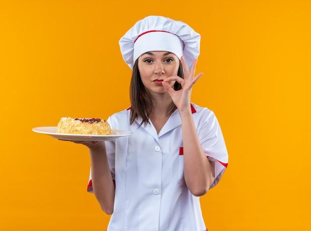 Tevreden jonge vrouwelijke kok die een chef-kok uniform draagt met cake op een bord met een heerlijk gebaar geïsoleerd op een oranje muur