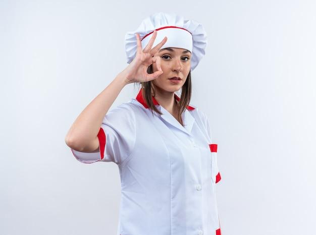 Tevreden jonge vrouwelijke kok die een chef-kokuniform draagt dat goed gebaar toont dat op witte muur wordt geïsoleerd