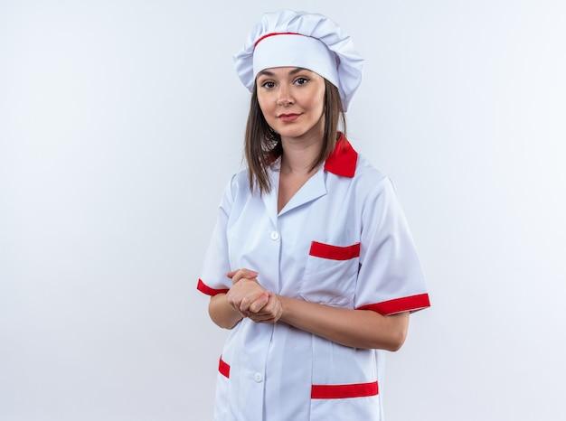 Tevreden jonge vrouwelijke kok die een chef-kokuniform draagt dat handdrukkengebaar toont dat op witte achtergrond wordt geïsoleerd