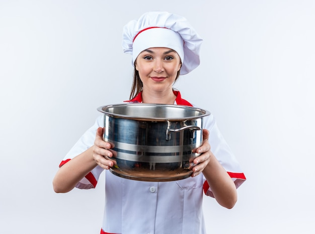 Tevreden jonge vrouwelijke kok die een chef-kokuniform draagt die een steelpan houdt die op witte muur wordt geïsoleerd