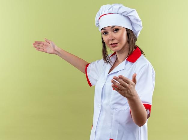 Tevreden jonge vrouwelijke kok die een chef-kokuniform draagt en doet alsof hij iets vasthoudt dat op een olijfgroene achtergrond is geïsoleerd