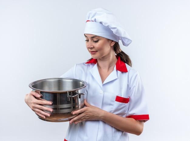 Tevreden jonge vrouwelijke kok die een chef-kokuniform draagt en naar een steelpan kijkt die op een witte muur wordt geïsoleerd