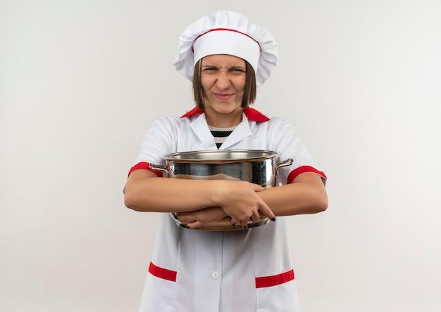 Tevreden jonge vrouwelijke kok in de pot die van de chef-kok de eenvormige holding voorzijde bekijkt die op witte muur wordt geïsoleerd