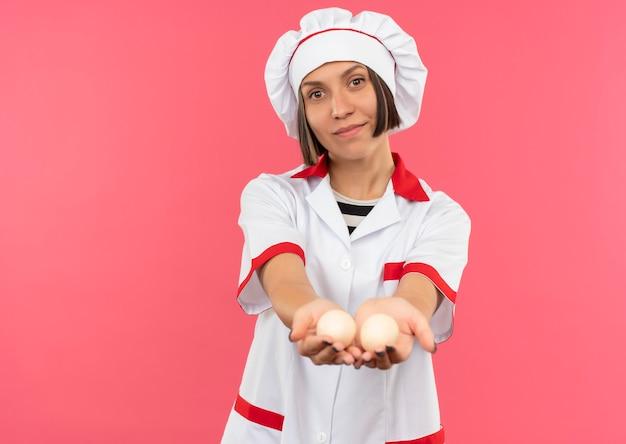 Tevreden jonge vrouwelijke kok in eenvormige chef-kok die eieren naar voorzijde uitstrekt die op roze muur wordt geïsoleerd