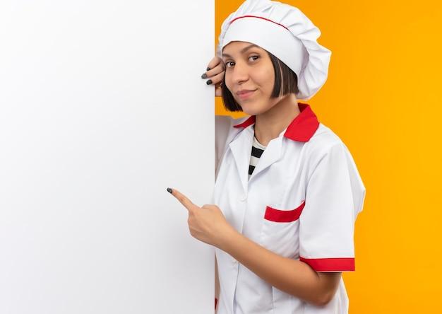 Tevreden jonge vrouwelijke kok in eenvormige chef-kok die zich achter bevindt en op witte muur richt die op muur wordt geïsoleerd