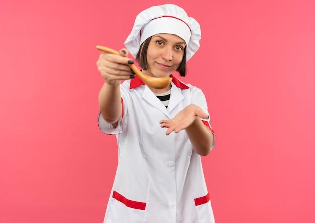 Tevreden jonge vrouwelijke kok in eenvormige chef-kok die zich lepel naar voren uitstrekt en lege hand toont die op roze muur wordt geïsoleerd