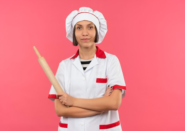 Tevreden jonge vrouwelijke kok in eenvormige chef-kok die zich met gesloten houding bevindt en deegrol houdt die op roze muur wordt geïsoleerd