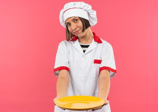 Tevreden jonge vrouwelijke kok in eenvormige chef-kok die zich uit plaat naar voren uitstrekt die op roze muur wordt geïsoleerd