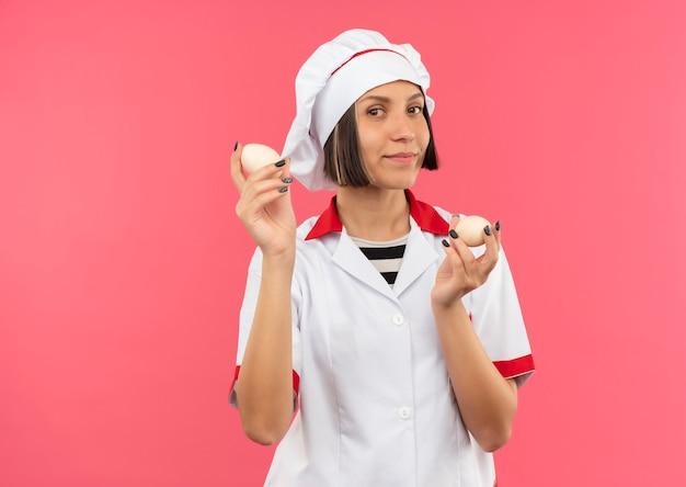 Tevreden jonge vrouwelijke kok in eieren van de chef-kok de eenvormige die op roze muur worden geïsoleerd