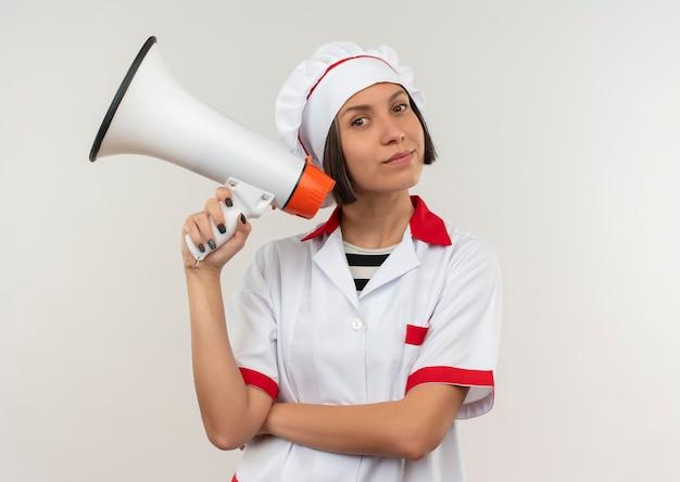 Tevreden jonge vrouwelijke kok in spreker van de chef-kok de eenvormige holding die op witte muur wordt geïsoleerd