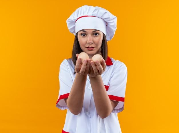 Tevreden jonge vrouwelijke kok in uniform van de chef-kok die eieren uitspuugt op camera geïsoleerd op een oranje achtergrond