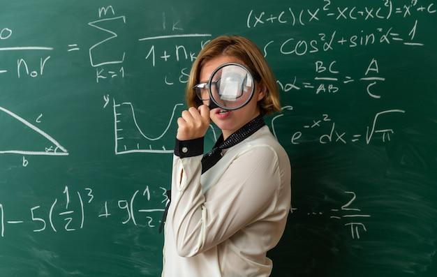 Tevreden jonge vrouwelijke leraar met een bril die voor het schoolbord staat en naar de camera kijkt met een vergrootglas in de klas
