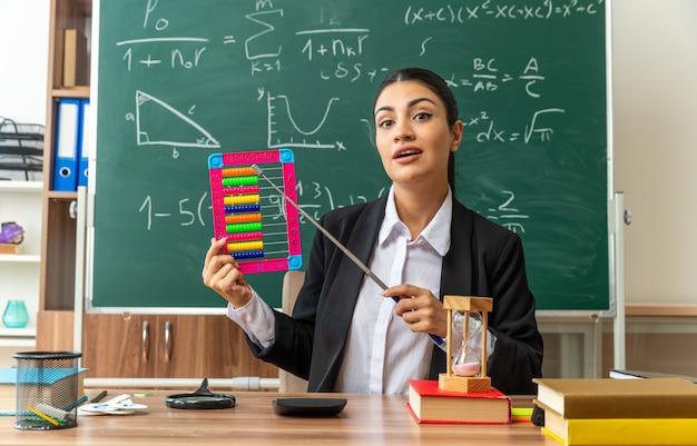 Tevreden jonge vrouwelijke leraar zit aan tafel met schoolbenodigdheden op telraam met aanwijzer in de klas