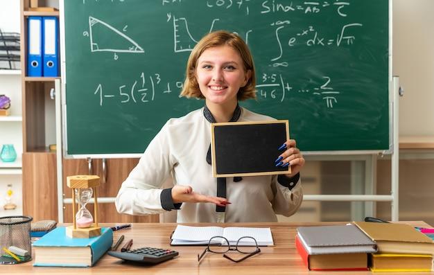 Tevreden jonge vrouwelijke leraar zit aan tafel met schoolgereedschap vast te houden en wijst met de hand naar mini-bord in de klas