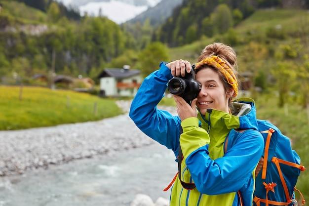 Tevreden jonge vrouwelijke reiziger maakt foto van berg- en rivierlandschap