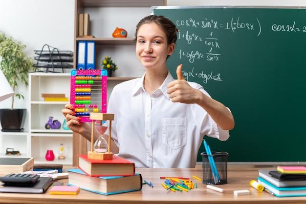 Tevreden jonge vrouwelijke wiskundeleraar die aan het bureau zit met schoolbenodigdheden die een telraam vasthoudt en naar de voorkant kijkt met duim omhoog in de klas