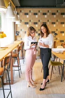 Tevreden jonge vrouwen op zoek naar designtrends via tablet en praten