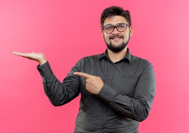 Tevreden jonge zakenman die glazen draagt die beweren iets te houden en punten die op roze muur worden geïsoleerd