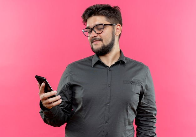 Tevreden jonge zakenman die glazen draagt die en telefoon bekijkt bekijkt