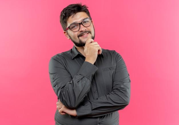 Tevreden jonge zakenman die glazen draagt die hand onder kin zetten die op roze muur wordt geïsoleerd