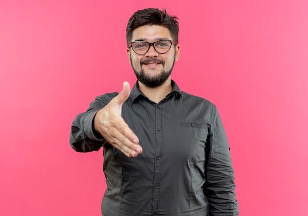 Tevreden jonge zakenman die glazen draagt die hand standhoudt die op roze muur wordt geïsoleerd
