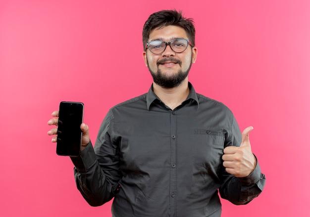 Tevreden jonge zakenman die glazen draagt die telefoon zijn duim houden omhoog geïsoleerd op roze muur