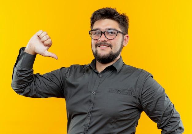 Tevreden jonge zakenman die glazen zijn duim draagt die neer op gele muur wordt geïsoleerd