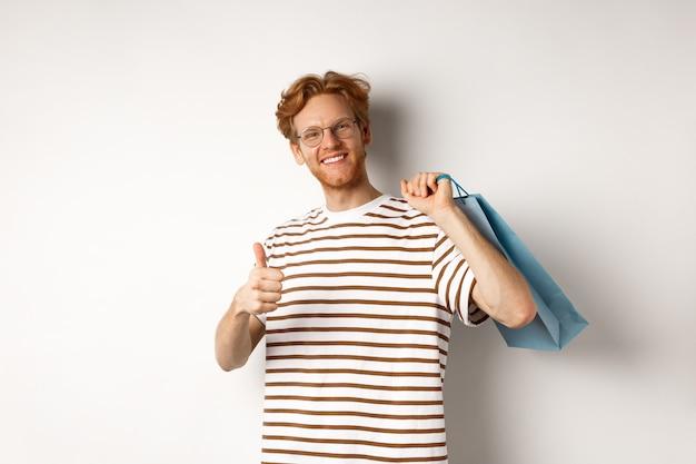 Tevreden jongeman laat een positieve recensie achter na het winkelen, toont duim omhoog in goedkeuring en glimlacht, houdt papieren zak over schouder, witte achtergrond.
