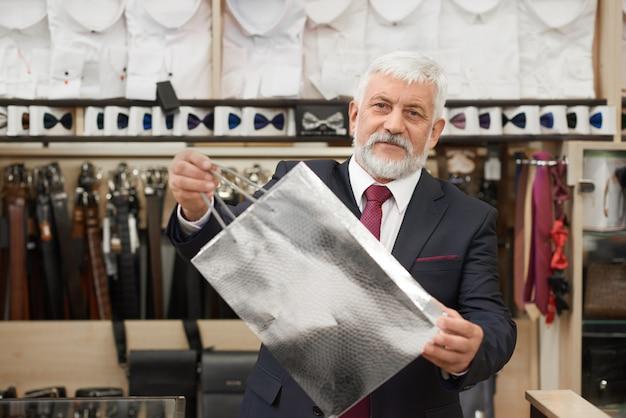 Tevreden klant bij het winkelen in mannelijke winkel.