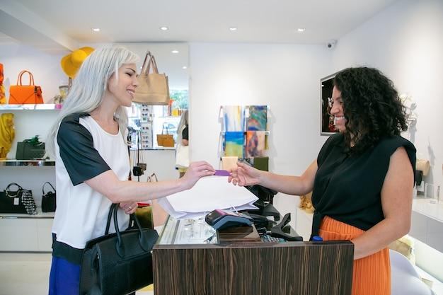 Tevreden klant creditcard geven aan kassier voor betaling voor aankopen, chatten, glimlachen en lachen. zijaanzicht. winkelen concept
