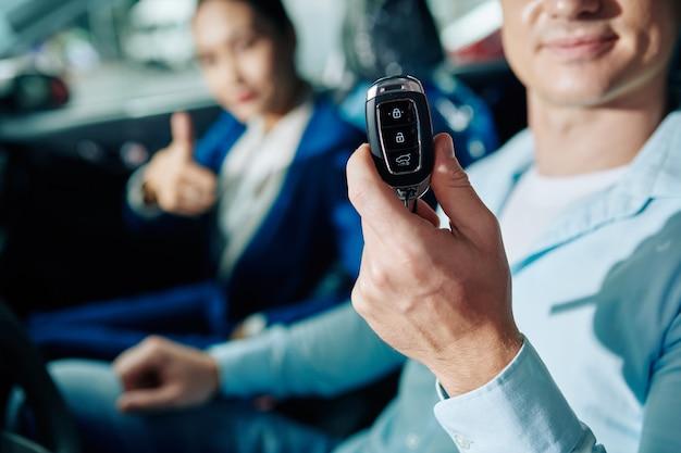 Tevreden klant die elektronische sleutels toont van auto die hij zojuist heeft gekocht