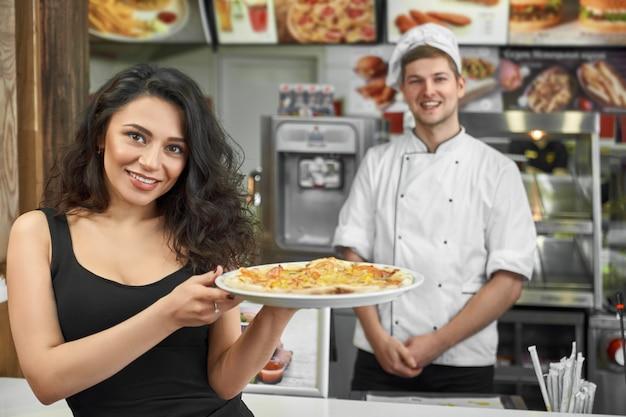Tevreden klant die pizza in handen houdt en in koffie stelt