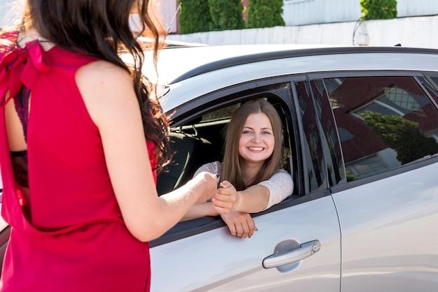 Tevreden klant en dealer met nieuwe auto buiten