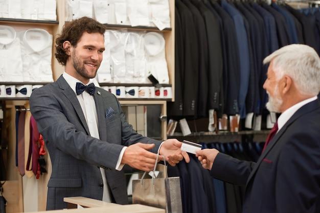 Tevreden klant het kopen van kleding in mode boetiek.